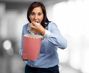 amazed young woman eating popcorn