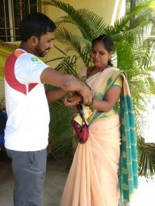 GOQii tech Personel helping Snehlata Satvi to wear teh band