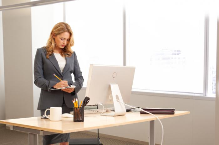 a-woman-standing-at-an-office-desk